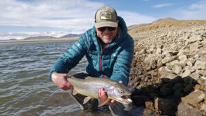 Jon Hill holds a nice trout while kneeling on shore